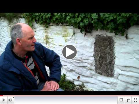Micheal Fox examines a Sheela Na Gig Stone Carving near Ardath, County Meath, Ireland