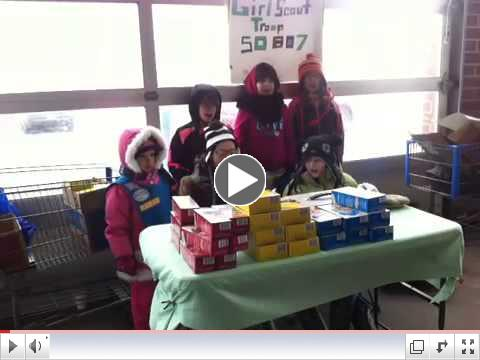 Troop 50807 sings at a cookie booth
